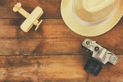 Odgórnego widoku wizerunek drewniany samolot, fedora kapelusz i stara kamera nad drewnianym stołem, Obrazy Stock