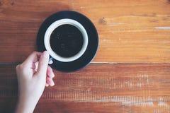 Odgórnego widoku wizerunek ręka trzyma filiżankę gorąca kawa Zdjęcia Stock