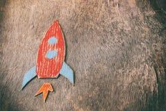 Odgórnego widoku wizerunek rakiety cięcie od papierowego i malujący nad drewnianym grunge tłem zdjęcie royalty free