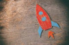 Odgórnego widoku wizerunek rakiety cięcie od papierowego i malujący nad drewnianym grunge tłem zdjęcia royalty free