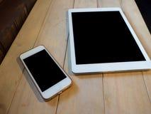 Odgórnego widoku wizerunek smartphone i pastylki przyrząd nad drewnianym stołem obrazy stock