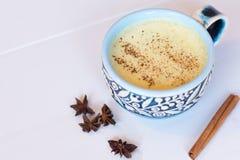 Odgórnego widoku wizerunek turmeric latte nad białym drewnianym stołem z copyspace Turmeric Latte z dokrętki mlekiem, cynamon, mi obrazy stock