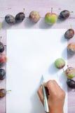 Odgórnego widoku zbliżenia ręki writing list, śliwkowych owoc drewniany tło Zdjęcie Stock