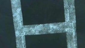 Odgórny 4k trutnia kamery powietrzny zakończenie w górę widoku na śmigłowcowego parking dużym liście h w okręgu znaku na górze bu zbiory
