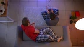 Odgórny strzał facet w sleepwear bawić się gra wideo i inny jeden relaksuje na kanapie i opowiada on w żywym pokoju zbiory