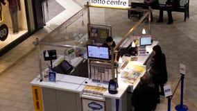 Odgórny strzał ludzie kupuje loteryjnego bilet wśrodku centrum handlowe loteryjnego bileta detalisty zbiory