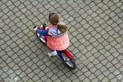 Odgórny widok ładna młoda dziewczyna patrzeje oddolny z długą jasnobrązową włosianą jazdą bicykl na chłodno wiosna dniu Outdoors  zdjęcie royalty free