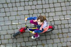 Odgórny widok ładna młoda dziewczyna patrzeje oddolny z długą jasnobrązową włosianą jazdą bicykl na chłodno wiosna dniu Outdoors  zdjęcia royalty free