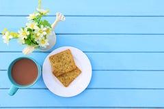 Odgórny widok śniadanie, błękitna filiżanka gorąca czekolada i krakersa chleb na białym naczyniu na błękitnym drewnianym stole, Zdjęcie Stock