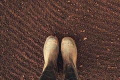 Odgórny widok średniorolni gumowi buty na przeorzącym grunt orny obraz royalty free