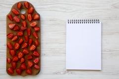 Odgórny widok, świeże truskawki na drewnianej desce z pustym notatnikiem Teksta teren Biały Drewniany stół Od above Obraz Stock