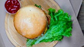 Odgórny widok świeży apetyczny hamburger wiruje na drewnianym talerzu zbiory