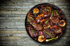 Odgórny widok świeży mięso i warzywo na grillu umieszczającym na drewnianej podłoga Fotografia Royalty Free