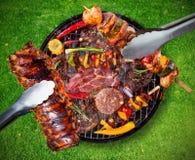 Odgórny widok świeży mięso i warzywo na grillu umieszczającym na trawie Zdjęcia Royalty Free
