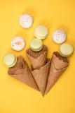 Odgórny widok żółci i biali macarons w gofrów rożkach na kolor żółty powierzchni Zdjęcia Royalty Free