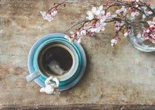 Odgórny widok błękitna rocznik filiżanka kawy z anioł figurką i wazą z wiosen gałąź na drewnianym tle obraz royalty free