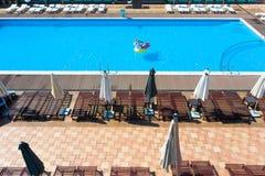 Odgórny widok basen z dziewczyną w swimsuit na nadmuchiwanym okręgu Relaksować i garbnikować w lecie zdjęcia stock
