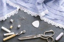 Odgórny widok bieliźniana tkanina, nić, nożyce, szy szpilki na wieśniaku siwieje powierzchnię zdjęcie stock