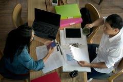 Odgórny widok biznesmeni i bizneswomany pracuje z raportami i laptopem zdjęcie stock