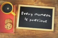 Odgórny widok blackboard z zwrotem każdy moment jest cenny obok filiżanki nad drewnianym stołem obrazy stock
