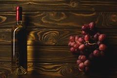 odgórny widok butelka biały wino i gałąź winogrona na drewnianym stole zdjęcie royalty free