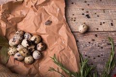 Odgórny widok cętkowani przepiórek jajka, gałązki rozmaryny, suszyć w górę podpalanych liści na lekkim drewnianym tle Zdjęcia Stock