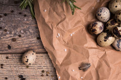 Odgórny widok cętkowani przepiórek jajka, gałązki rozmaryny, suszyć w górę podpalanych liści na lekkim drewnianym tle Obrazy Royalty Free