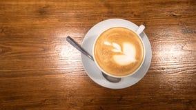 Odgórny widok cappuccino kawa z sztuką ubiera up w białej filiżance na okrzesanym drewnianym stole Zdjęcia Royalty Free