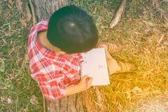 Odgórny widok Chłopiec writing na książce jest edukacja starego odizolowane pojęcia ilustracyjny lelui czerwieni stylu rocznik Obrazy Royalty Free
