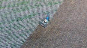 Odgórny widok ciągnik który orze pole disking ziemię Glebowa kultywacja po żniwa Zdjęcie Stock