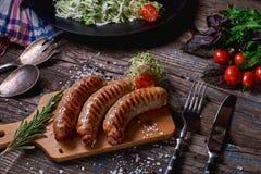 Odgórny widok colorfuls smażył kiełbasy i warzywa na nieociosanym drewnianym stole Kiełbasy na grill niecce na drewnianym tle Zdjęcie Royalty Free
