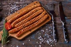 Odgórny widok colorfuls smażył kiełbasy i warzywa na nieociosanym drewnianym stole Kiełbasy na grill niecce na drewnianym tle Fotografia Royalty Free