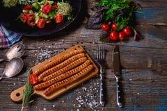 Odgórny widok colorfuls smażył kiełbasy i warzywa na nieociosanym drewnianym stole Kiełbasy na grill niecce na drewnianym tle Obrazy Stock
