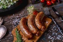 Odgórny widok colorfuls smażył kiełbasy i warzywa na nieociosanym drewnianym stole Kiełbasy na grill niecce na drewnianym tle Fotografia Stock