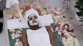 Odgórny widok cosmetologist wręcza stosować zdrową gliny maskę na młodej Afrykańskiej żeńskiej twarzy Kobieta k?ama z relaksem zdjęcie wideo