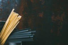 odgórny widok czarny i klasyczny linguine makaron w niecce obraz stock