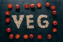 Odgórny widok czerwoni dojrzali pomidory w formie rama i list kształtował chickpeas na ciemnym tle Weganinu jedzenia poj?cie orga obrazy royalty free