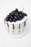 Odgórny widok domowej roboty kwaśnej śmietanki tort dekorował z winogronami i lawendą na białym drewnianym tle Obrazy Stock