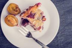 Odgórny widok domowy piec śliwkowy kulebiak słuzyć na talerzu dla deseru Obraz Royalty Free