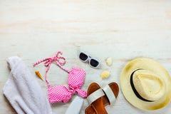 Odgórny widok dwa kawałka różowi pływackiego kostium i plażowych accessoties nad drewnianym tłem Odbitkowy space= Fotografia Royalty Free