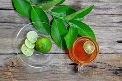 odgórny widok filiżanka herbata, cytryna pokrajać i zieleni cytryna opuszcza Fotografia Stock