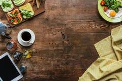odgórny widok filiżanka kawy, pastylka, tablecloth i śniadanie, zdjęcia royalty free