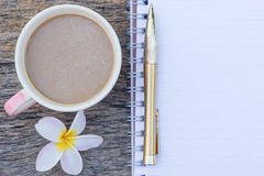 odgórny widok filiżanka z Plumeria kwiatem i puste miejsce notatnikiem Fotografia Stock