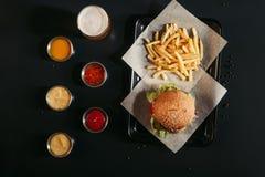 odgórny widok francuzów dłoniaki i smakowity hamburger na tacy, szkle piwo i asortowanych kumberlandach, fotografia royalty free