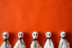 Odgórny widok Halloween rzemiosła, papierowy duch na pomarańcze papieru tle fotografia royalty free