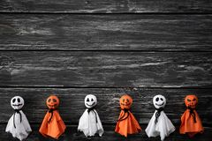 Odgórny widok Halloween rzemioseł, bielu i pomarańcze papierowy duch na czarny i biały drewnianym tle, obraz royalty free