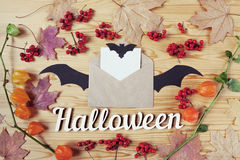 Odgórny widok Halloweenowy drewniany pulpit z papierem, kopertą, nietoperzem, jagodami i liśćmi klonowymi, Z kopii przestrzenią Fotografia Royalty Free