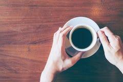 Odgórny widok Hand& x27; s mężczyzna chwyt filiżanka gorąca kawa na starym drewnianym ta Obraz Stock