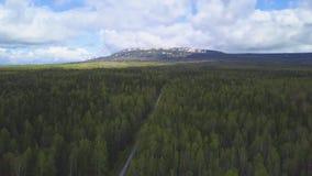 Odgórny widok horyzont z wiejską drogą między lasem i niebem klamerka Skalista góra na horyzoncie iluminującym słońcem przeciw zbiory