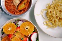 Odgórny widok i zamyka w górę obiadowego stołu, sałatki i Fettuccine bolończyka umieszczającego na, fotografia royalty free